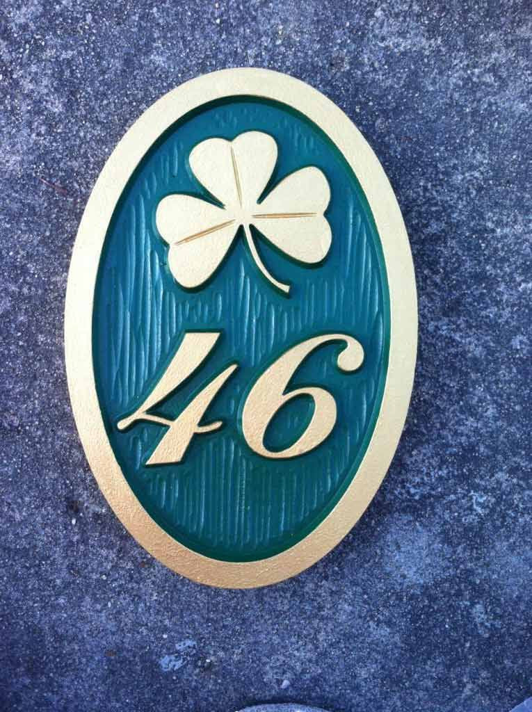 Custom carved house number address sign with a shamrock and 46 oval shape painted green and gold