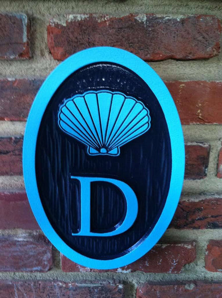Custom carved house number address sign with a scallop shell and D oval shape painted navy blue and light blue