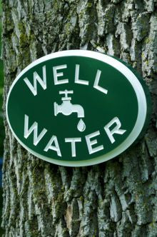 Well water sign hung on tree