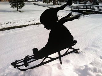 Silhouette of child going down hill in snow