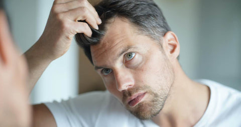 man looking at hair in the mirror considering Low Level Laser Therapy for Hair Loss