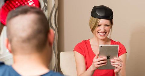 woman on ipad determining if Laser Cap Therapy or Finasteride is more effective