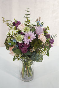 Purple spray mums, eucalyptus, and fresh, local flower arrangement in a glass vase