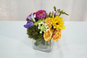 small flower arrangement in a cube glass vase