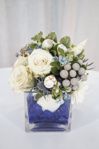 ocean themed vase arrangement, white flowers like roses and carnations with sea shells