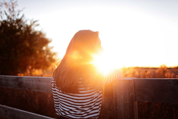 young woman leaning on a fence with sun setting in front