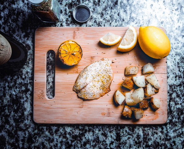wooden chopping board with cooked fish, potatoes and lemon and a bottle of wine