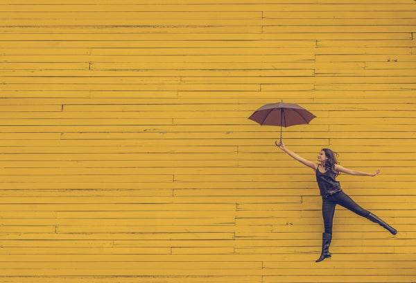 happy women with umbrella yellow wall - so sweaty blog stress & weight loss