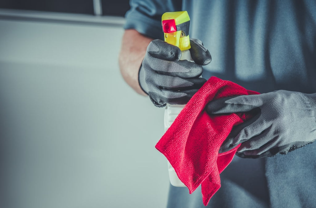 A Man Holding Detergent and Cleaning Cloth.