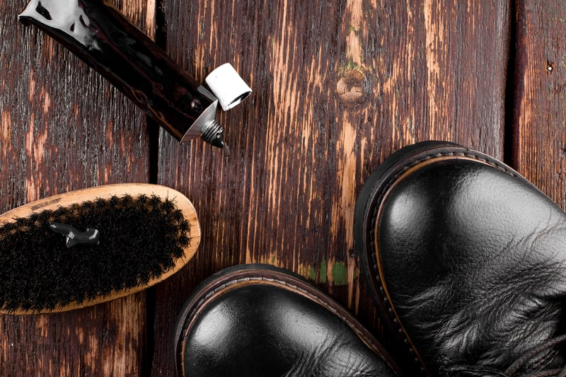 Black Boots on Wooden Background With Polishing Equipment, Brush and Polish Cream.