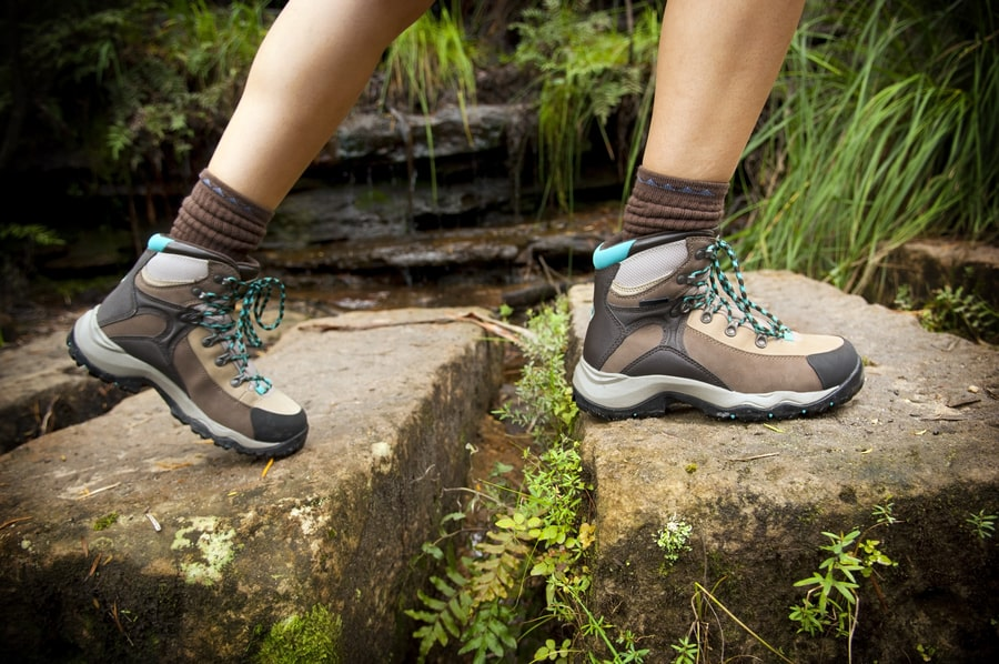 Hiker crosses stone steps in hiking boots.