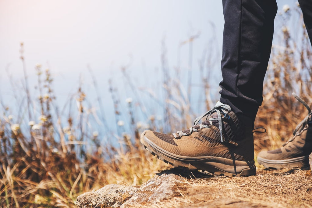 Closeup of a hiking boots on the top of hill.
