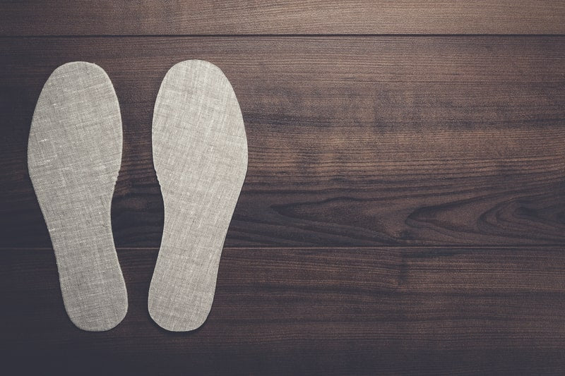 Grey Insoles for Shoes on Wooden Background.