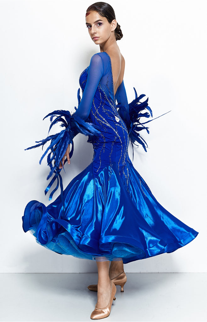 Ballroom dress in intense royal blue colour, siren like silhouette, with full pearl chiffon skirt, long stretch net sleeves with luxury rooster feather detailing and satin ribbons for the arms.  The dress is fully decorated with blue, turquoise and white Swarovski crystals, in different shades and sizes.