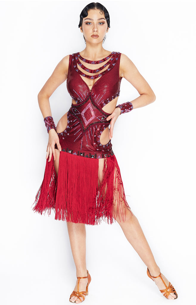African inspired latin dress in a special burgundy hologram lycra, decorated with different shades and hues of Swarovski crystals, reds, blues, burgundy and siam stones. Built in cups and leotard, cut-out details.  Currently in stock size XS-S.  This stunning, fully completed, ready to wear Latin DanceSport Dress can be created in any colour and size.