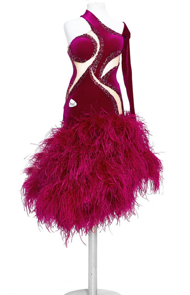 Special junior and youth latin dress with full ostrich feather skirt in fuchsia pink, top in smooth velvet with stretch net nude insertions. The body is decorated with Fuchsia, Fuchsia Ab and Rose Swarovski crystals along the nude insertions. Full back, asymmetrical sleeve and slit on the skirt, perfect for Junior II and youth category dancesport.
