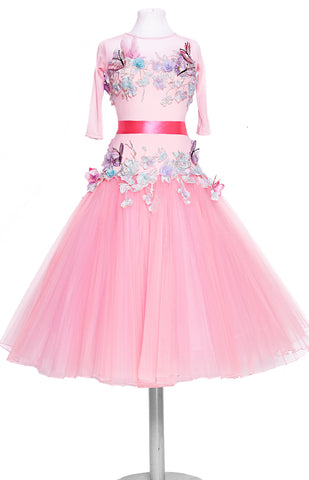 Junior ballroom dress, in sugar pink, with tulle stiff net pleated skirt, decorated with pastel coloured flowers, petals, and butterflies.  Pink satin ribbons around the wrists and waist.   This stunning, fully completed, ready to wear Junior Ballroom DanceSport Competition Dress can be created in any colour and size.