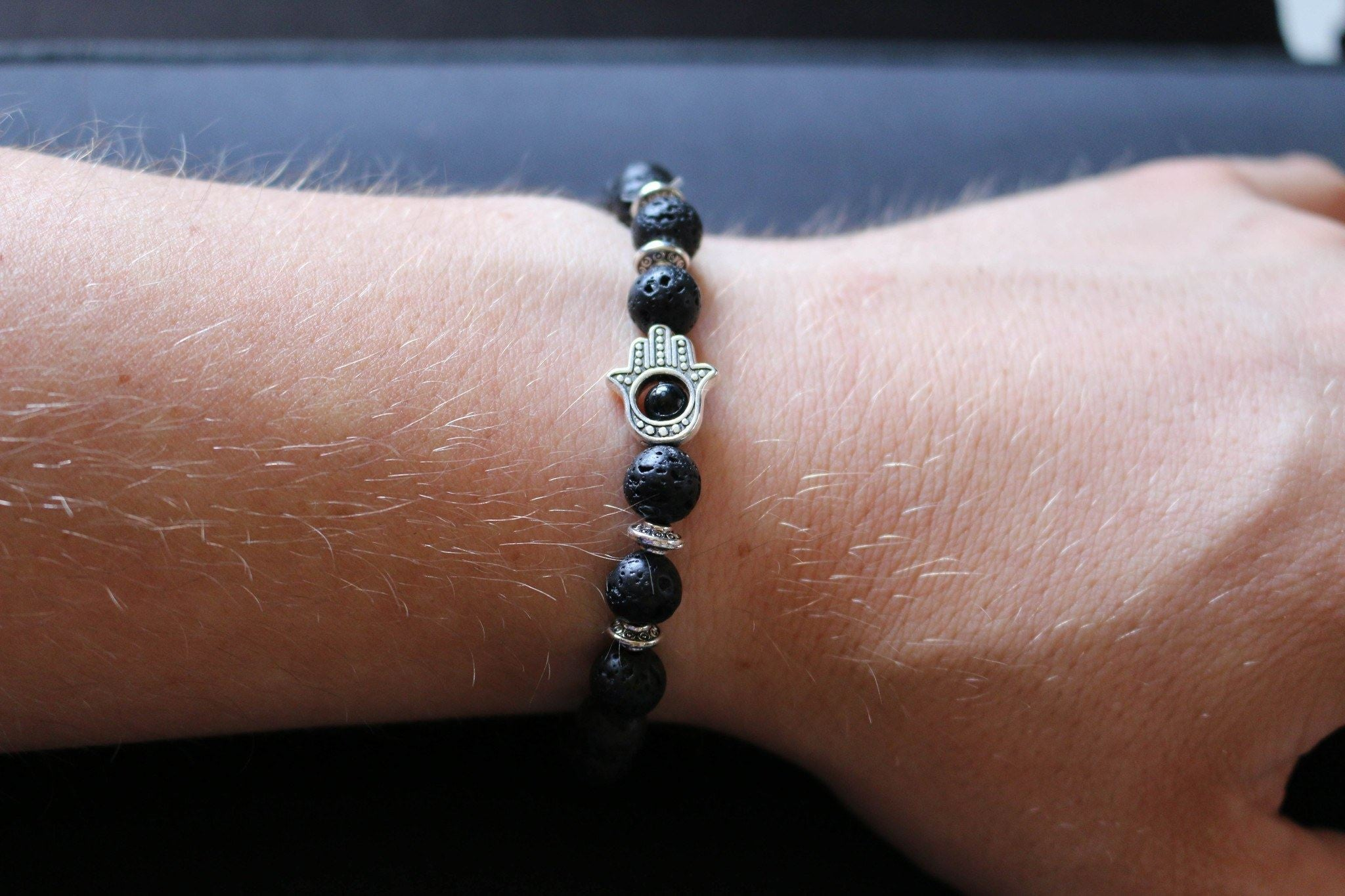 Lava Stone Bead Bracelet With Silver Hamsa Charm on wrist