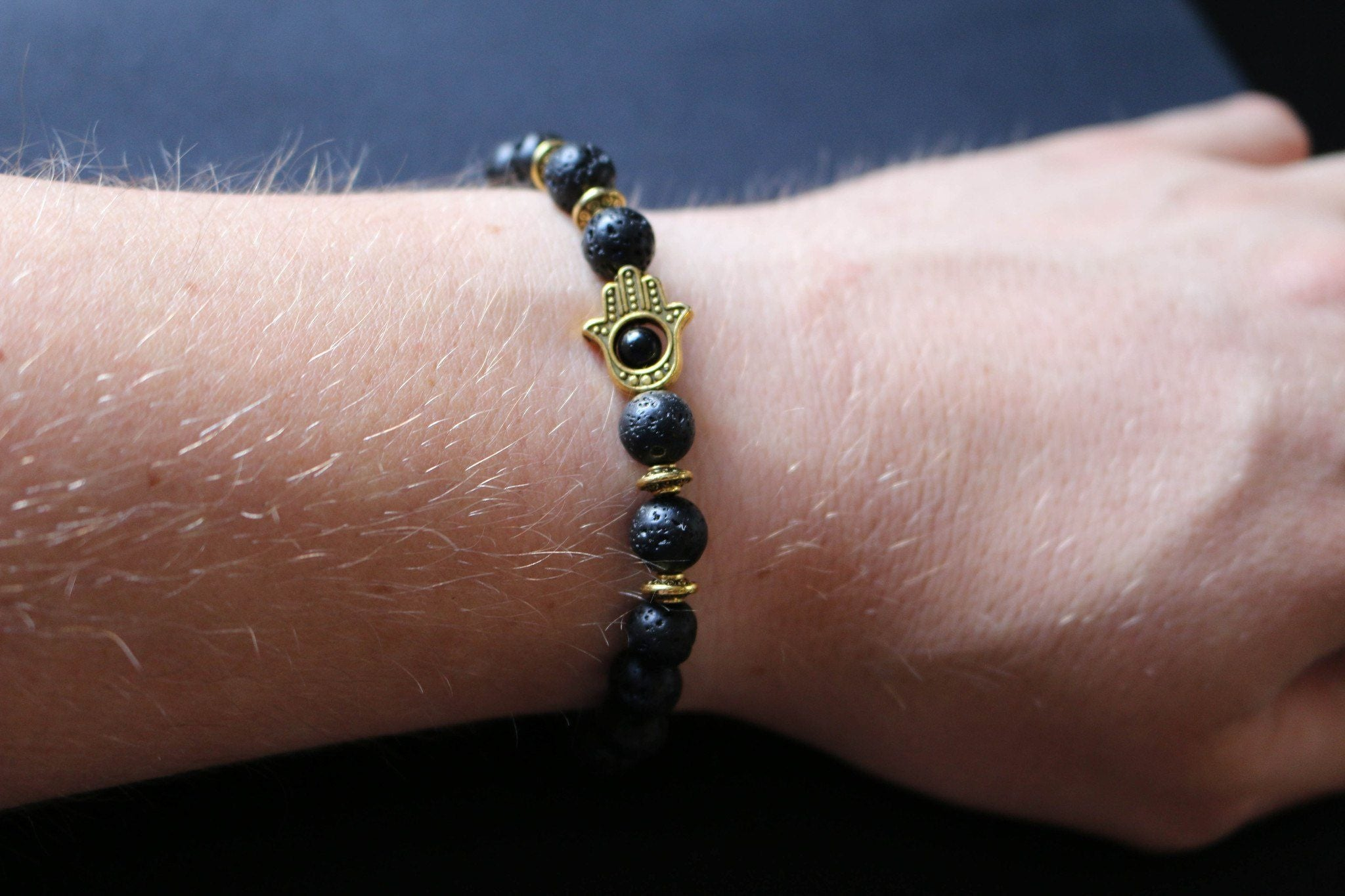 Lava Stone Bead Bracelet With Gold Hamsa Charm on wrist