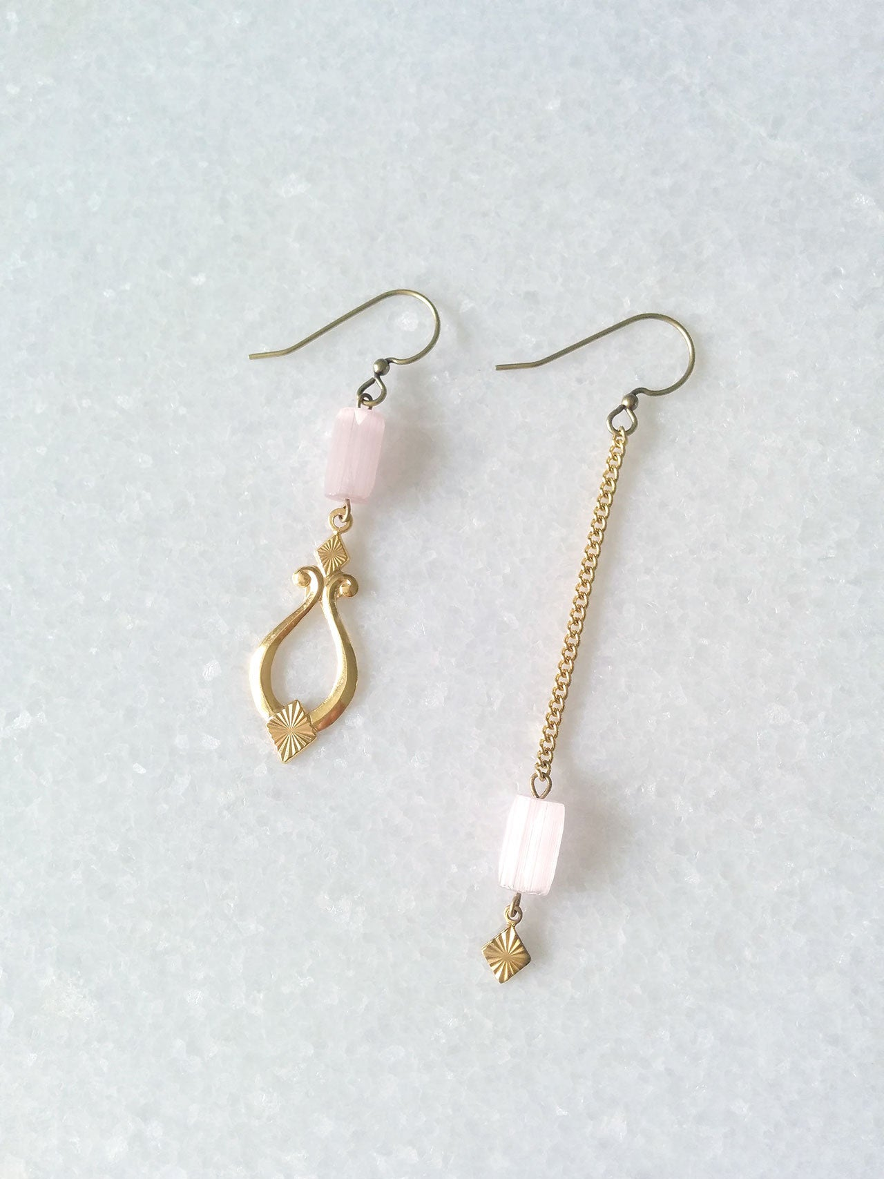 Mismatched earrings pale pink