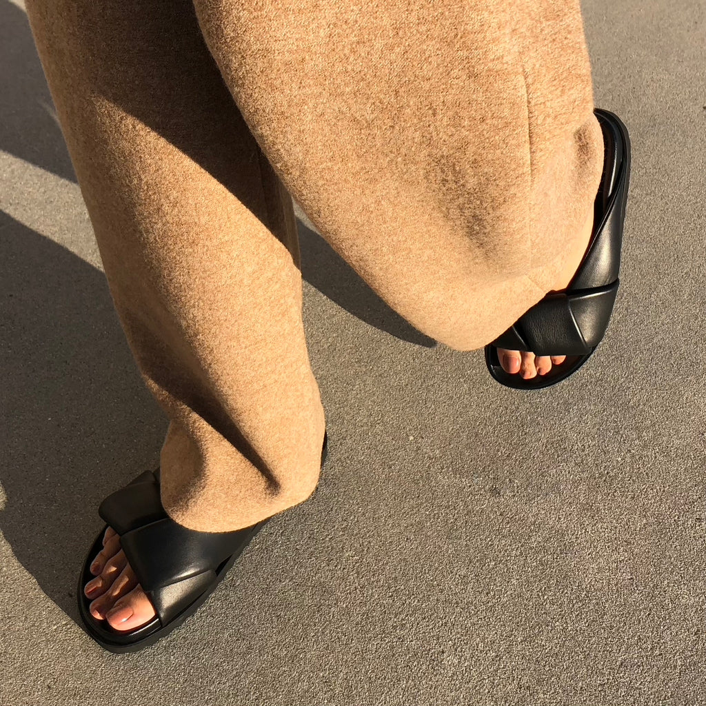 Neil J Rodgers black Obi slide sandal with padded leather straps, comfortable flat footbed and lightweight thick black sole paired with camel cashmere pants.