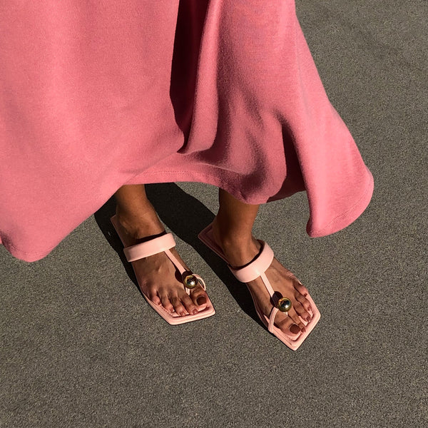 Neil J Rodgers pink Samira sandal with a flat footbed, minimal leather straps and gold bead embellishment paired with a pink midi dress.
