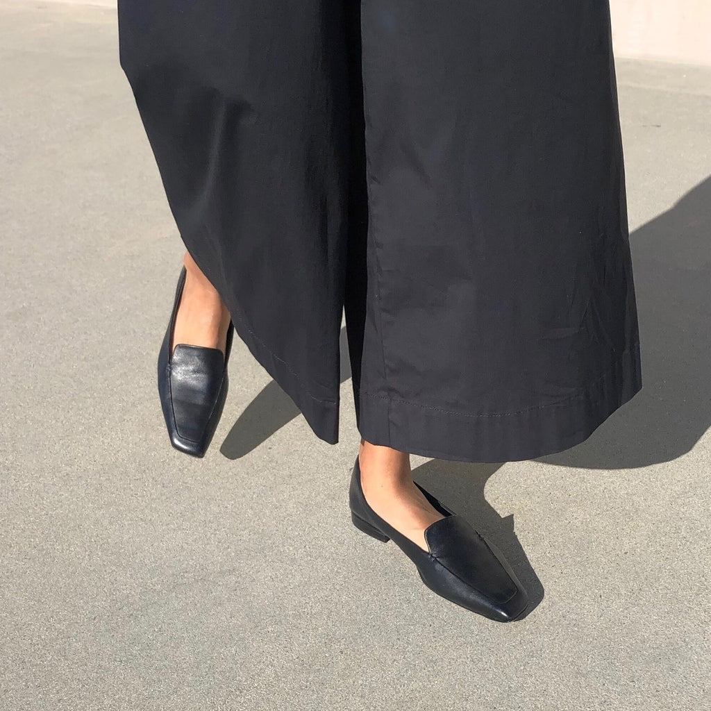 Neil J Rodgers black Liscia loafer with a pointed square toe and minimal stitching in soft Italian nappa leather paired with wide leg, lightweight black pants.