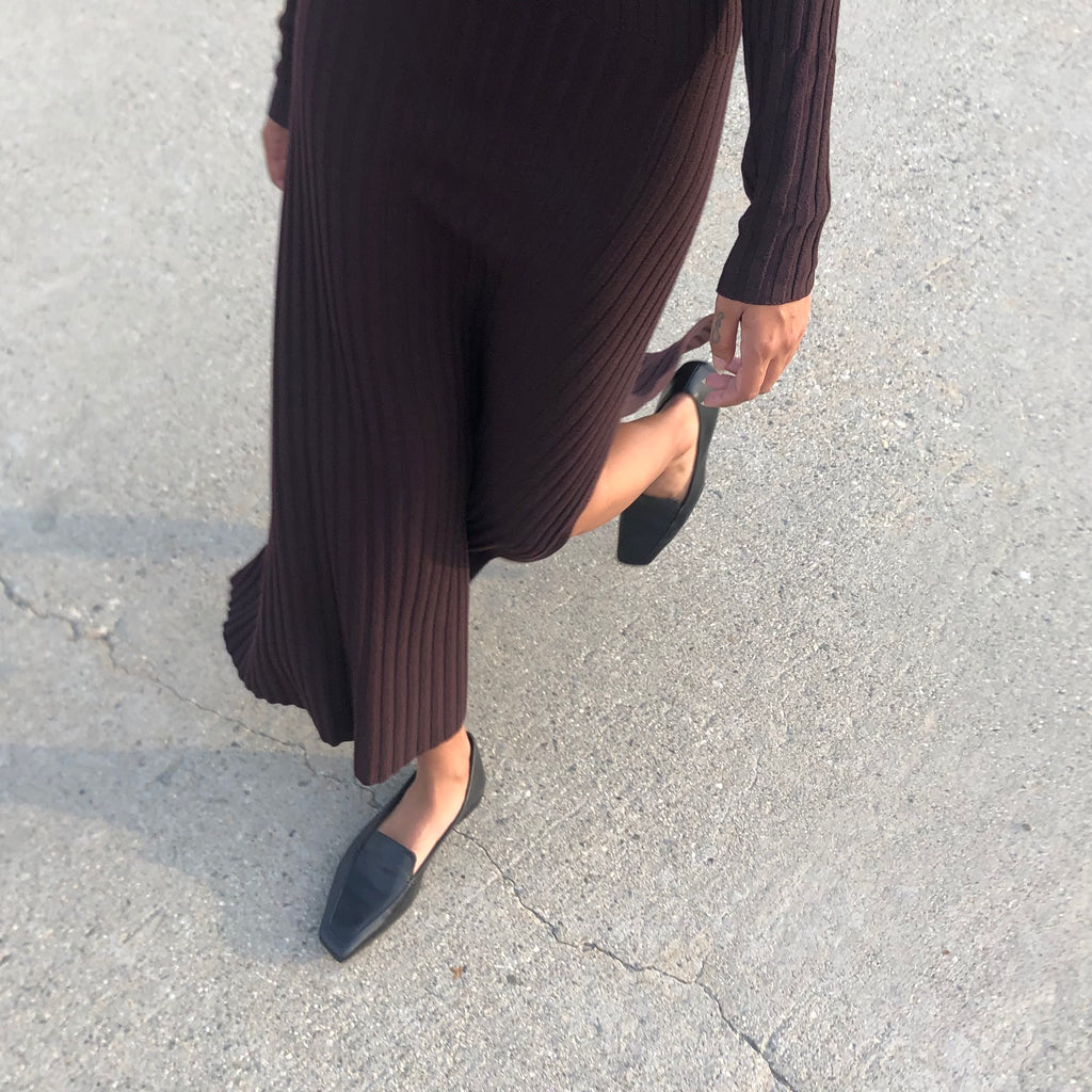 Neil J Rodgers black Liscia loafer with a pointed square toe and minimal stitching in soft Italian nappa leather paired with a brown ribbed sweater dress.