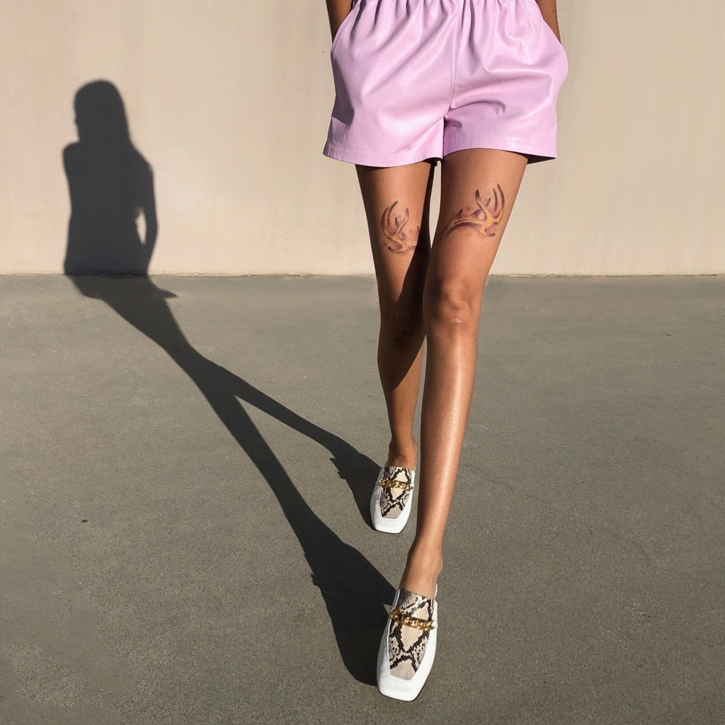 Neil J Rodgers white and python print Laura loafer with chain detail and comfortable block heel paired with pale pink leather shorts.