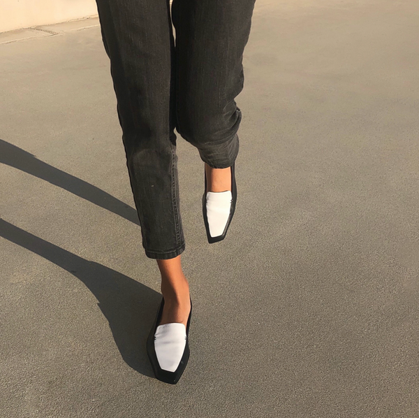 Neil J Rodgers black and white Liscia loafer with a pointed square toe and minimal stitching in soft Italian nappa leather paired with black straight leg denim.