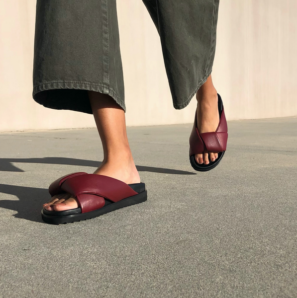 Neil J Rodgers burgundy Obi slide sandal with padded leather straps, comfortable flat footbed and lightweight thick black sole paired with black wide leg denim pants.