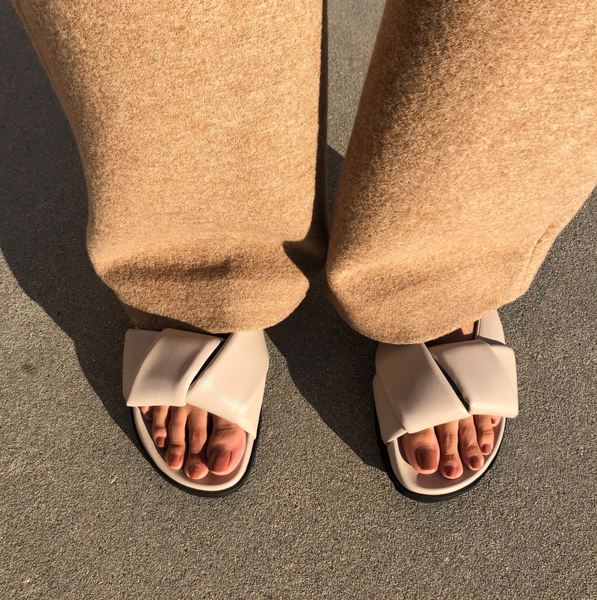 Neil J Rodgers off-white Obi slide sandal with padded leather straps, comfortable flat footbed and lightweight thick black sole styled with camel cashmere pants.