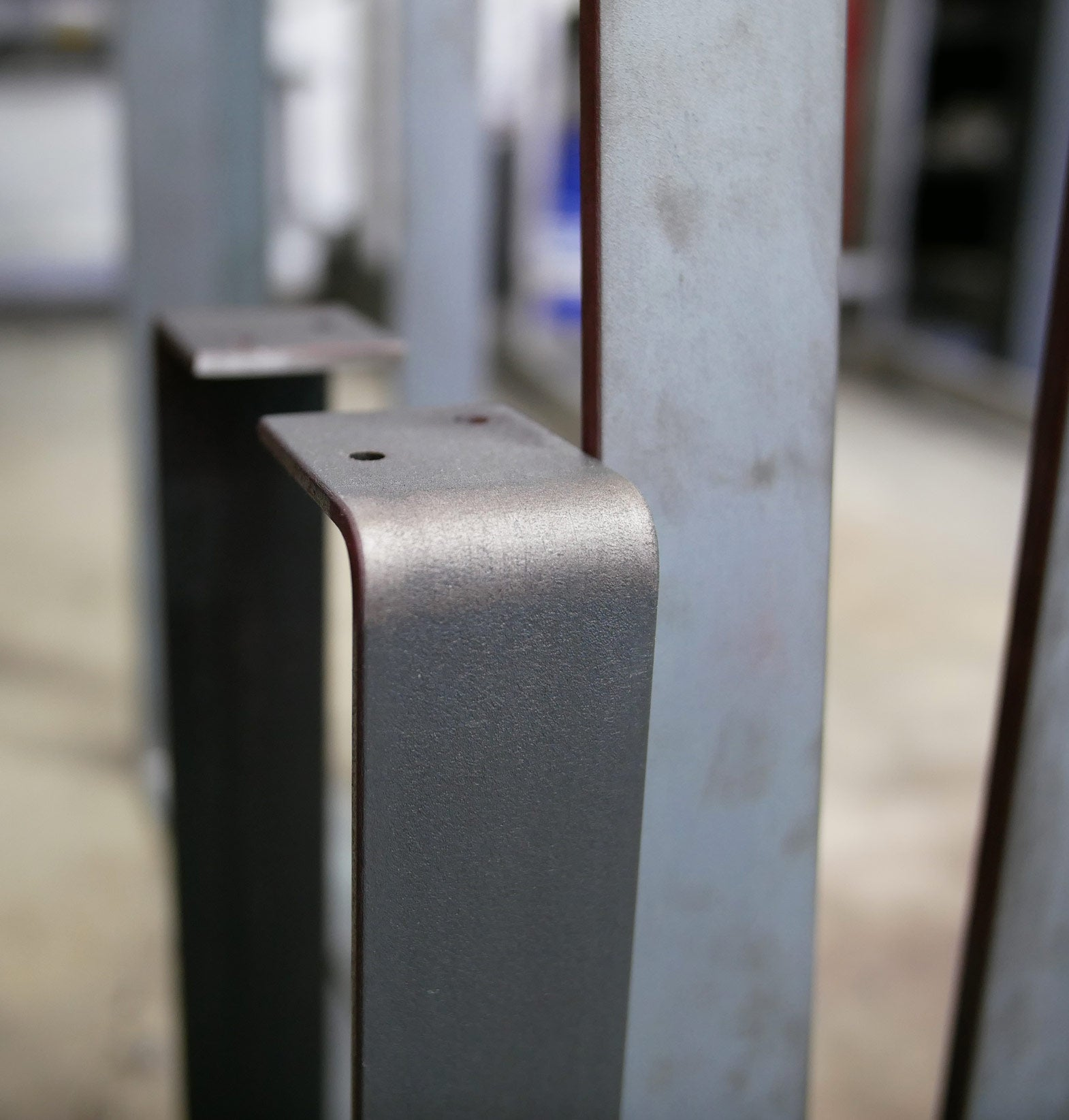 Metal table legs showing clear sealant finish on the left and unfinished steel on the right