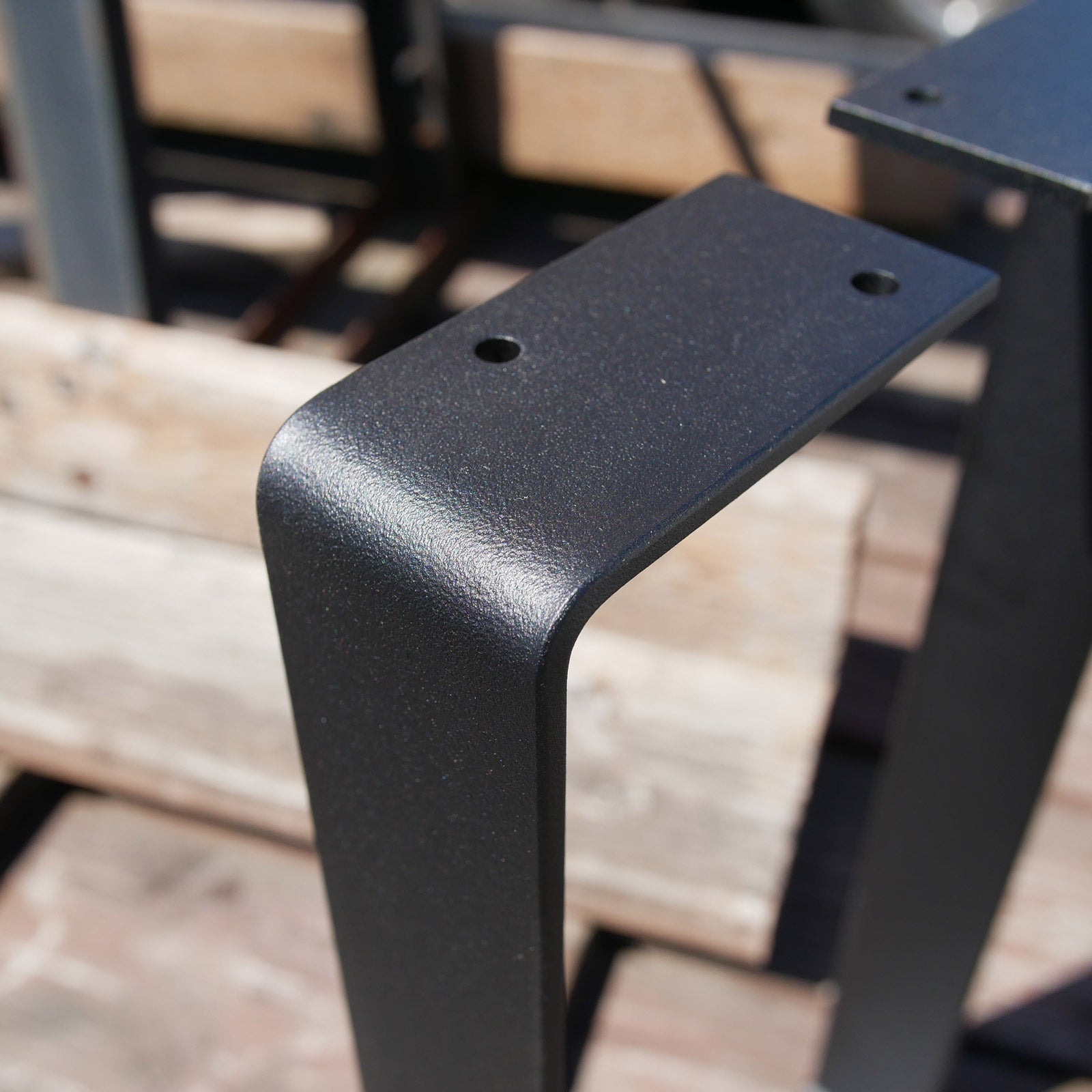 Black powder coat on flat bar steel in direct sunlight
