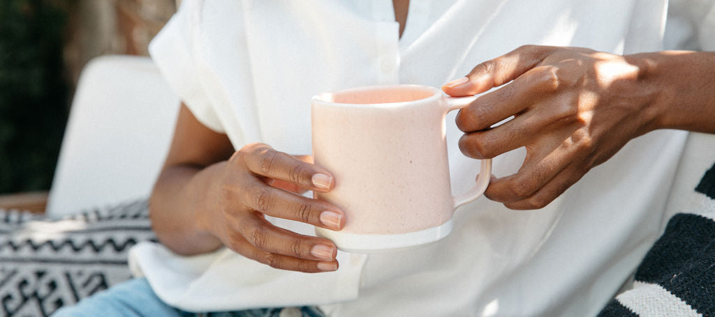 hands holding pink handmade mug by Paper & Clay