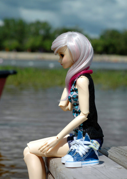 pink haired ball joined doll in summer sitting on a dock of lake
