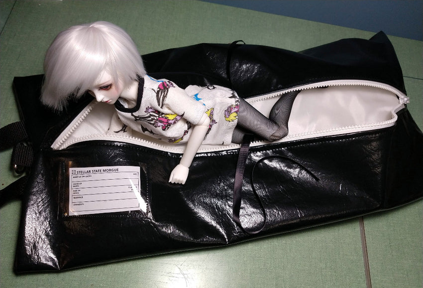 zombie doll emerges from her body bag