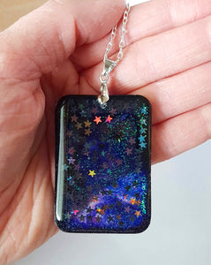 dark galaxy pendant handmade by stellar evolution designs