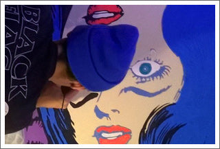 Jeff Nolan working on a pop art painting of a trippy comic book girl with Marie Nolan.