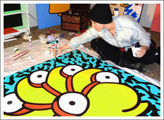 "Palm Treat artist Marie Williams at work in the studio on a Lisa Frank inspired pop art painting of Milhouse from the hit FOX show ""the Simpsons"" in 2015"