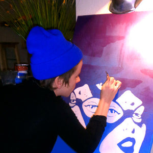 Marie Williams, Marie Nolan Palm Treat artist painting folk outsider vaporwave art trippy Catwoman artwork in the studio. Technicolor cartoon pop art by a beautiful art girl.