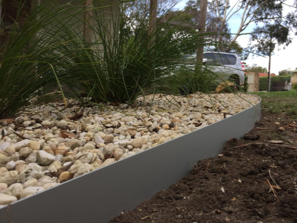 Core Edge Flexible Steel Lawn Edging shown in Light Grey as border of flower bed - Henderson Garden Supply
