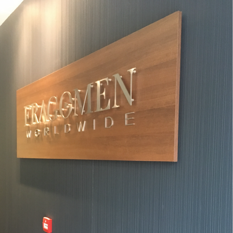 Reception sign at Fragomen Dublin featuring a walnut panel and brushed stainless steel lettering fixed to the wall to give a floating illusion. Signage by Barrow Signs