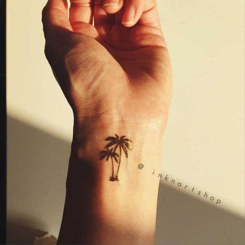 Tiny palm tree tattoo on wrist