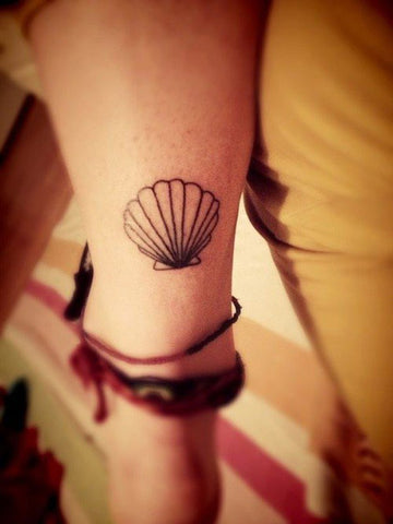 tiny shell tattoo on woman