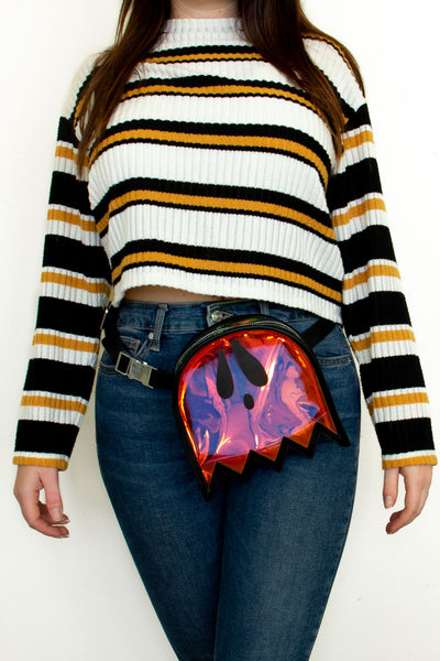 A cute outfit of a fanny pack with high waisted jeans and a sweater.