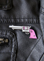 pink gun enamel pin on a black leather jacket