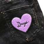 A purple furry heart patch with a quote in cursive font on the back of women's black jeans.
