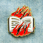 "A free speech enamel pin of a burning book with the quote, ""Censorship is Dictatorship""."