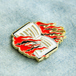 A black, red, and gold enamel pin of a burning book celebrating first amendment rights..